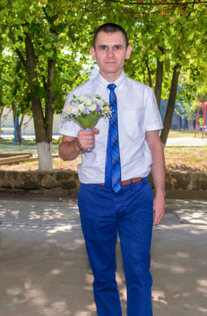 shirtsleeves: Happy bridegroom arriving for his wedding carrying the bridal bouquet with a beaming smile