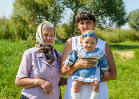 three generations of women: Three family generations of women with a loving grandmother, daughter and granddaughter posing together outdoors in a park on a sunny summer day with the cute little baby smiling happily at the camera Stock Photo