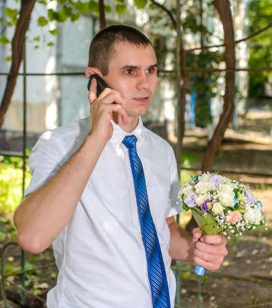 arboles frondosos: Hombre que sostiene un ramo de flores en el chat en un teléfono móvil mientras se está al aire libre bajo la sombra de árboles frondosos escuchando con una expresión seria