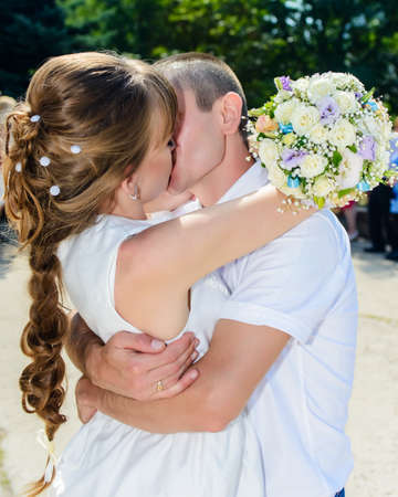 Loving newlyweds enjoy a romantic kiss hugging each other tightly outdoors in the sunshine in a close up view
