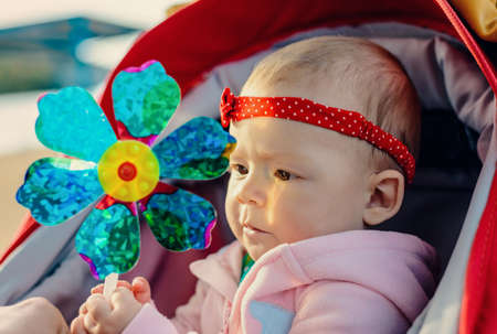 Adorable happy smiling little baby girl wearing a stylish red headband and bow sitting in a carrycot with her fingers in her mouth, close up head and shoulders