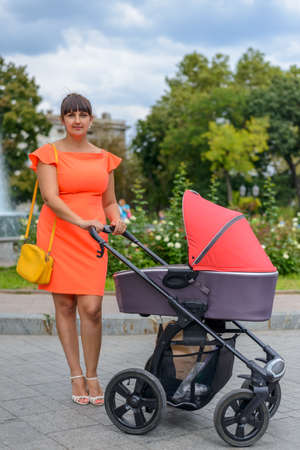Caring mother in a stylish orange summer outfit, bending forward attending to her infant baby in a pram on an urban road