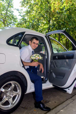godfather: Smiling man holding bouquet of flowers in car
