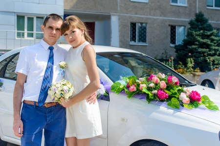 arm bouquet: Young bridal couple standing arm in arm near the wedding car decorated on the hood with a colorful bouquet of flowers