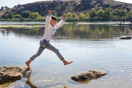 Jonge jongen springen van rots naar rots langs de oevers van een rustig meer op een zonnige zomerdag als hij geniet van zijn vakantie Stockfoto