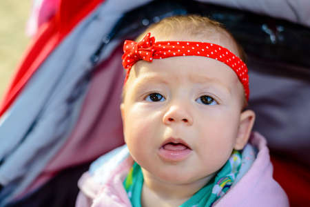 Fascinated little baby girl watching the camera with her mouth open as she sits quietly in a pram or push-chair outdoors wearing a pretty red headband and bow Stock Photo