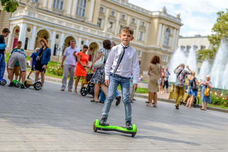 Stylish young boy riding a hover board in an urban park standing balancing on it facing the camera with a smile photo