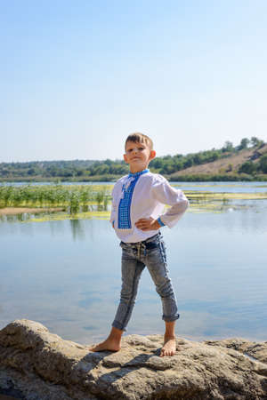 Proud little boy posing on a rock on the shore of a calm rural lake with his hands on his hips and head held high photo