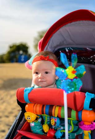 al pequeño bebé lindo que lleva una diadema roja que se sienta en un colorido cochecito o cochecito de niño mirando con curiosidad a la cámara Foto de archivo