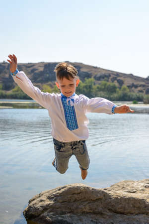 Small boy playing on rocks at the lake jumping from one to another with his arms outstretched and a smile of pleasure photo