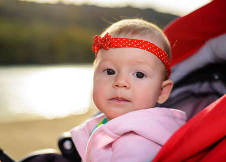 Serene little baby girl wearing a red headband with bow sitting in a push-chair outdoors at a lake staring intently at the camera Stock Photo