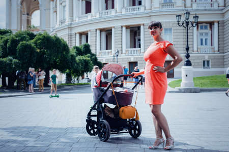Stylish mother in a colorful orange dress pushing her baby in a pram across a paved urban square in summer sunshine Stock Photo