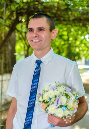 Happy bridegroom arriving for his wedding carrying the bridal bouquet with a beaming smile