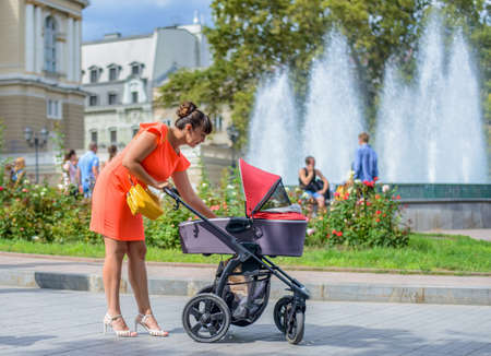 Stylish mother attending to her infant baby in a pram on a paved urban walkway with people visible behind in the distance