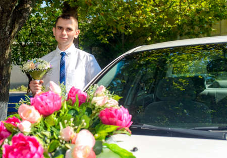 godfather: Man holding bouquet while standing near car