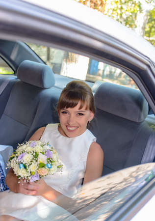 Pretty young bride in the back of the bridal car sitting peering intently at the camera with her bouquet of fresh flowers in her hand