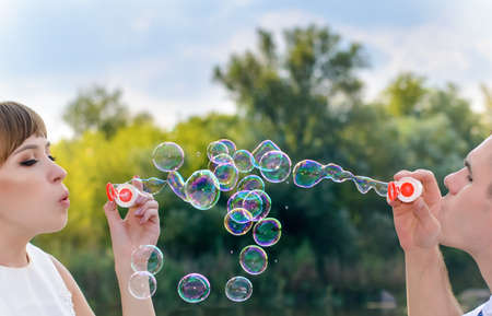 in unison: Romantic young bride and groom blowing bubbles as they celebrate their recent marriage together outdoors in nature, close up of their faces and the bubbles