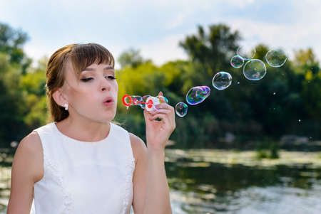 Happy young bride blowing bubble to celebrate her wedding as she stands alongside a river after the ceremony