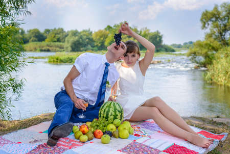 Young bridal couple sharing a meal of fresh fruit together as they sit on a blanket on the edge of a river bank celebrating after the wedding ceremony