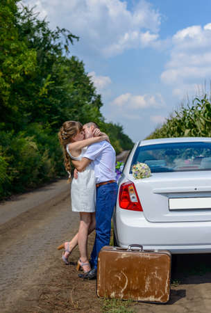 Loving newlywed couple stopping their car in a maize field on a rural road for a romantic hug and kiss, with copy space
