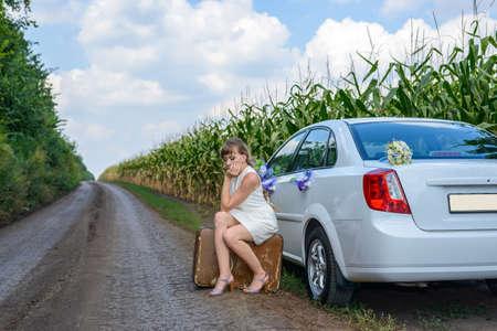 mujer golpeada: Mujer joven varados en audiencia borde de la carretera en una vieja maleta maltratada junto a un coche adornado con flores en un campo de maíz joven Foto de archivo