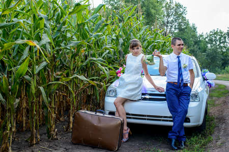 ignoring: Young newly wed bridal couple having their first marital argument sitting on the bonnet of their car parked in a corn field facing away and ignoring each other with a suitcase in front of them Stock Photo