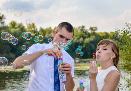in unison: Newlywed young bride and groom celebrating together after the ceremony blowing colorful iridescent soap bubbles on a river bank Stock Photo