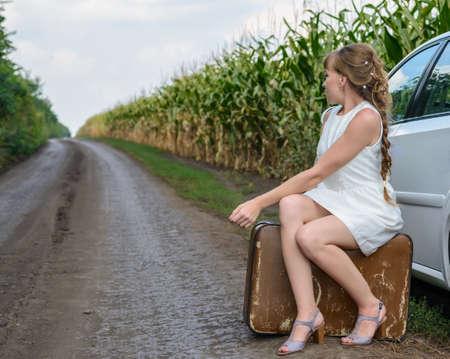 mujer golpeada: coche nupcial desglosado en el borde de la carretera en un carril rural a través de un campo de maíz joven con la mujer joven que se sienta en una maleta maltratada junto a él a la espera de la asistencia Foto de archivo