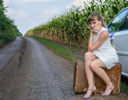 woman resting: Bridal car broken down at the roadside on a rural lane through a field of young maize with the young woman sitting on a battered suitcase alongside it waiting for assistance