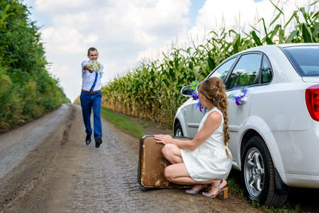crouches: Bridegroom running towards his newly wed wife holding out the bridal bouquet as he makes up after an argument as she crouches in the road alongside her suitcase