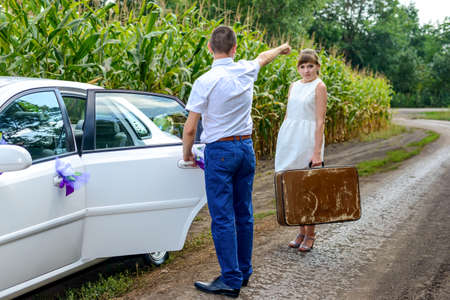 Newlyweds having their first argument with the young woman leaving the bridal car with her suitcase and walking off down a farm road with her suitcase as her husband waves goodbye behind her Stock Photo
