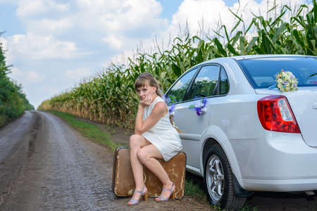 Young woman stranded at the roadside sitting on a battered old suitcase alongside a car decorated with flowers in an field of young corn