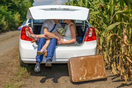 obscured: Unidentifiable married couple obscured by car trunk outside beside cornfield. Large brown suitcase on ground.