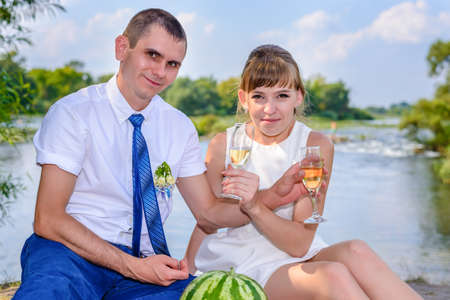 Romantic young newlywed couple celebrating together outdoors on a river bank sitting on a rug drinking champagne with entwined arms