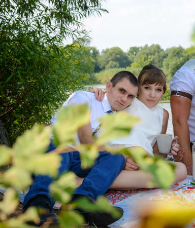 Young newlywed couple relaxing on a rug alongside a river after the wedding ceremony as they celebrate their marriage with friends Stock Photo