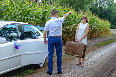 dominant: Newlyweds having their first argument with the young woman leaving the bridal car with her suitcase and walking off down a farm road with her suitcase as her husband waves goodbye behind her Stock Photo