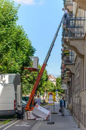 Frankrijk, Strasburg 23 juni 2016: Hulpmiddelen die meubels uit een bovenverdieping leveren of verzamelen met behulp van een mechanische lift of hysbak tijdens het verwijderen van de straat in een stedelijke omgeving