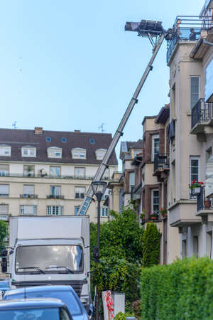 Haulers delivering or collecting furniture from an upstairs apartment using a mechanical lift or hoist during removals viewed from the street in an urban environment