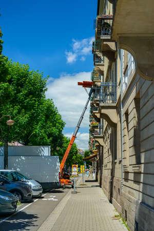 Francia, Estrasburgo 23 de junio de 2016: Camionetas que entregan o recogen muebles de un piso de arriba utilizando un elevador o elevador mecánico durante las mudanzas vistas desde la calle en un entorno urbano Foto de archivo - 81749430