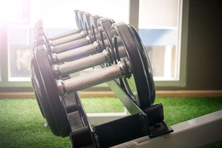 weight training: dumbbell in gym - vintage effect and sun flare filter effect Stock Photo