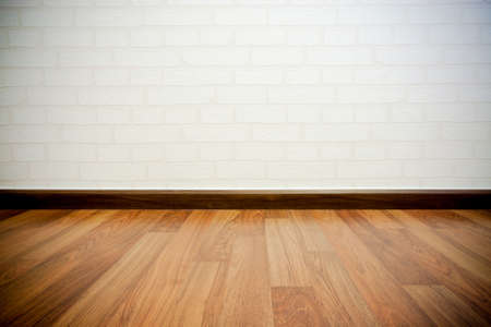 Copyspace の背景、テキストまたは広告の大きなコピー スペース下堅木張りの木製床の空の白いレンガ壁に 写真素材