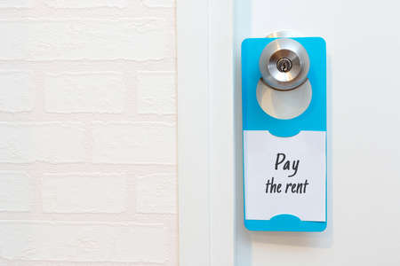 knobs: A door hanger write a message pay the rent on a door, with copy space