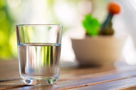 vaso con agua: vaso de agua sobre fondo de madera mesa de bokeh - imagen de estilo vintage
