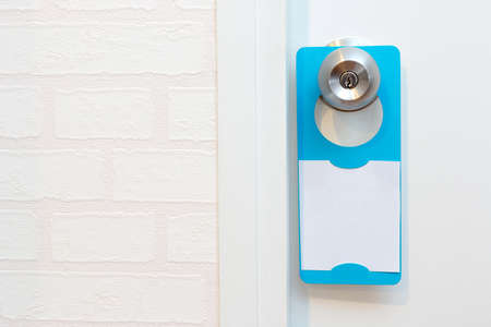 add text: A blank door hanger on a door, with copy space, add text or graphic