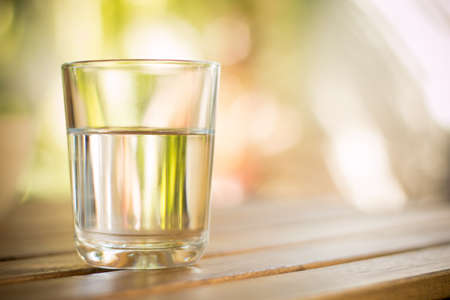 water garden: glass of water on wooden table bokeh background - vintage style picture