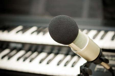 estudio de grabacion: Cerca de un micrófono durante la sesión de grabación con un cantante, piano en el fondo Foto de archivo