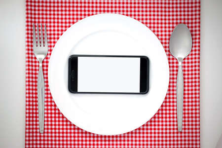 food absorption: Smartphone on white dish or plate between spoon, fork on red classic checkered tablecloth texture on white table with copy space for advertise food product and other