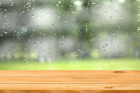 Mesa de madera vacía sobre la gota de agua en el fondo de la ventana del jardín. Listo para la exhibición de productos de montaje.