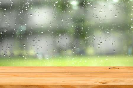kropla deszczu: Pusty drewniany stół na kropli wody na okno tle ogrodu. Produkt gotowy do wyświetlania montażu. Zdjęcie Seryjne