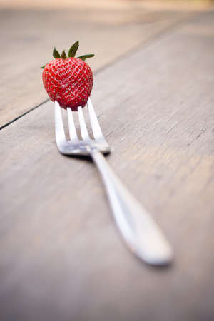sappy: Selective focus strawberry on a fork over wooden table - filter vintage style picture